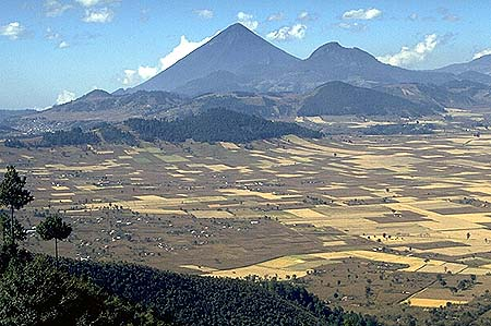 Here is a classically-formed strato volcano called Santa Maria, in Guatemala. Santa Maria had a huge eruption in 1902, from a vent on the other side of the cone as viewed from this direction. The big 1902 eruption was not from the summit. Starting in 1929, a lava dome began to grow in the 1902 crater, and it is still active today. It is named Santiaguito. The relatively large city of Quetzaltenango is out of view to the right.