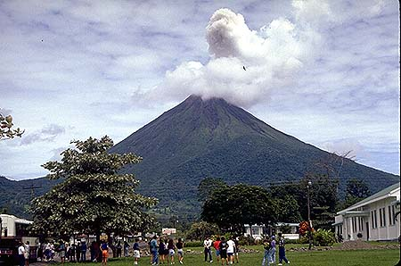 This is Arenal volcano, in Costa Rica. It is almost perpetually erupting at a relatively low rate. You can sort of get a sense for how small most strato volcanoes are - you could easily hike around the base of Arenal in a day. As you can see there are people living very near to this active volcano. Fortunately, at the moment most of the lava flows and small pyroclastic flows are going down the other side of the volcano, not the side with this town.